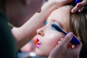A young boy has make up applied for LGBT+ parade